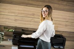 Business woman working in office by the printer. Young business woman working in office by the printer royalty free stock photo