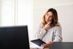 Business Woman working at the Office taking phone call royalty free stock image