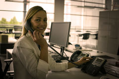 Business woman working in office. Woman talking on Landline phone Royalty Free Stock Images