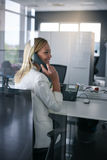 Business woman working in office. Woman talking on Landline phone Royalty Free Stock Image
