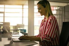 Business woman working in office. Woman typing on laptop Royalty Free Stock Images