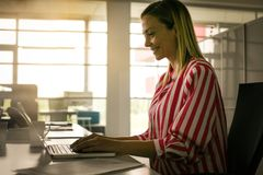 Business woman working in office. Woman typing on laptop. Portrait royalty free stock photo