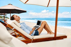 Business Woman Working Online On Beach. Freelance Computer Internet. Business Woman Working Online On Laptop Computer Lying On Sun Loungers At Beach. Portrait Stock Photography