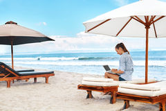 Business Woman Working Online On Beach. Freelance Computer Internet. Business Woman Working Online On Laptop Computer Lying On Sun Loungers At Beach. Portrait Royalty Free Stock Photo