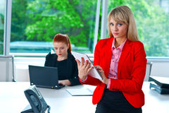 Business woman working on tablet with colleague in background Royalty Free Stock Images