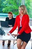 Business woman working on tablet with colleague in background Royalty Free Stock Photo