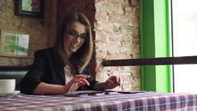 Business woman working with a tablet and rejoice in cafe. 4k stock video footage