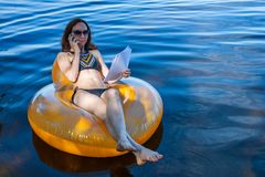 Business woman working on vacation, remote work. Woman talking on mobile phone while sitting in an inflatable ring royalty free stock photos