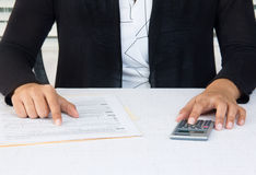 Business woman at workplace working on financial accounts. Business person in black suit working on financial accounts in office stock photography