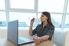 A business woman works at a computer in a restaurant and drinks wine from a glass. Lifestyle. Woman is relaxing at work. Stock Images