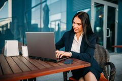 Business woman works on laptop in office. Modern building, financial center, cityscape. Female businessperson in suit at workplace Royalty Free Stock Photography