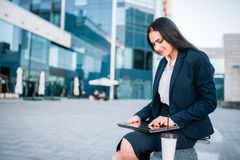 Business woman works on laptop outdoor. Modern building, financial center, cityscape. Female businessperson in suit Stock Photos