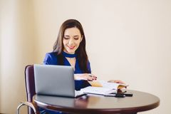 Business woman works with notes and laptop royalty free stock photography