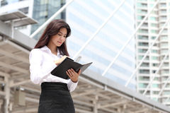 Business woman write massage on her book with behind modern buil Royalty Free Stock Photography