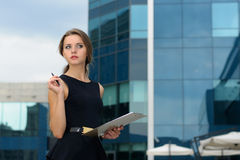 Business woman writes in a folder with documents Stock Image