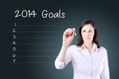 Business woman writing blank 2014 goals list. Blue background. Royalty Free Stock Photography