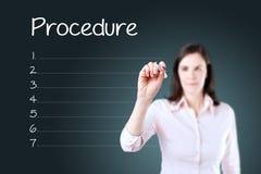 Business woman writing blank procedure list. Blue background. Stock Photos