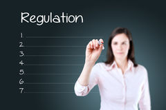 Business woman writing blank regulation list. Blue background. Business woman writing blank regulation list. Blue background Stock Images