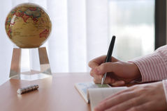 Business woman writing a cheque with globe spinning Royalty Free Stock Image