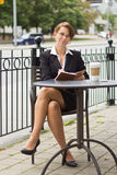 Business woman writing in journal at outdoor cafe Royalty Free Stock Image