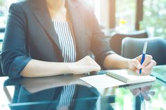Business woman writing on a notebookwith a pen in the office Royalty Free Stock Photo
