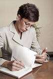 Business Woman Writing with pen in notepad Royalty Free Stock Image