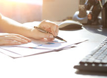 Business Woman Writing with pen in office Stock Photo