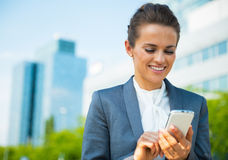 Business woman writing sms in office district Stock Photo