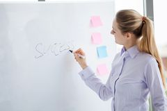 business woman writing success on white board in office, work place meeting room stock image