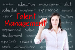 Business woman writing talent management concept. Blue background. Stock Photos