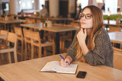 Business woman writing to do list in a cafe Stock Photography