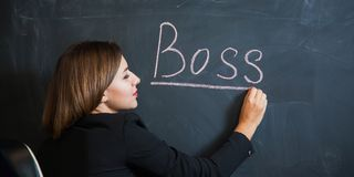 Business woman writing the word boss on desk. Royalty Free Stock Photography