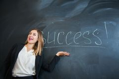 Female office worker put down text success on black board Royalty Free Stock Image