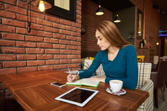 Business womanl working on  digital tablet. Modern business woman working on  digital tablet and  writing in a notebook while sitting at coffee shop interior Royalty Free Stock Photography
