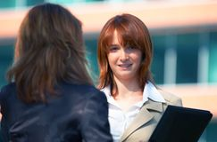 Business Women. Two business women discussing a proposal in front of an office building Royalty Free Stock Photo