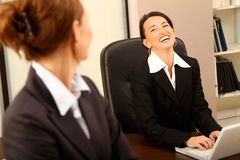 Business Women. Two business women laughing at the office stock photo