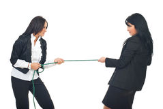 Business women competition. Two business women in competition pulling rope isolated on white background Stock Photography