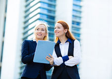 Business women discussing new project outside corporate office Stock Photos