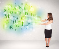 Business women with glowing letter concept Stock Photo