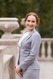 Business women in grey suit. Smiling business woman in grey suit on the air Stock Photography