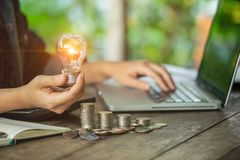 Business women hand holding light bulb on stack coins and working with computer on workplace. Creative ideas concept of saving mon royalty free stock images
