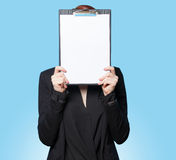 Business women hiding behind tablet. Business woman hiding behind tablet on blue background Royalty Free Stock Photos