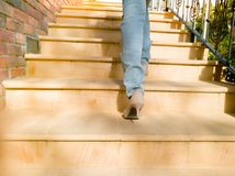 A business women in high hills is stepping on stair for successful stock images