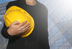 business women hold yellow safety hat on Skyscraper background. Stock Images