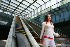Business women holding mobile phone on escalator Stock Photo