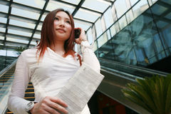 Business women holding mobile phone and newspaper Stock Photo