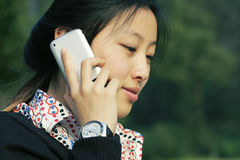 Business women holding  phone. Asian business women holding a mobile phone in park Royalty Free Stock Images