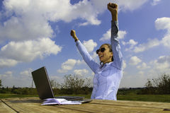 A  women with a laptop, sitting in the garden and make a great deal,  she happy with her arms up Stock Images