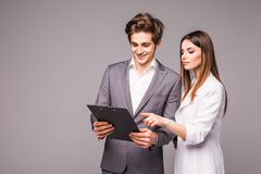 Business woman and business man pointing finger at blank isolated on gray background stock photography