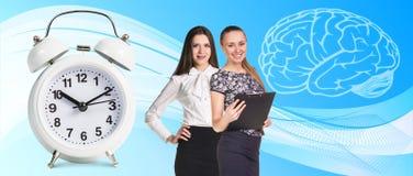 Business women near classical alarm clock Stock Image